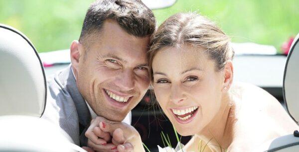 Couple In Convertible Taking Wedding Photos